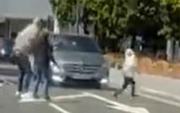 Heart-stopping moment a young child narrowly avoids being hit by a car as he dashes into a busy road while running across with an adult