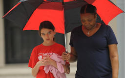Suri Cruise Takes Shelter Under Her Nanny's Umbrella During Rainy Outing in New York City — See Pics!