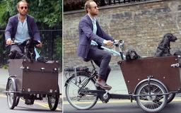 That's one way to walk the dog! James Middleton enjoys a relaxed cycle through London as his inquisitive pets peer out from his cargo bike