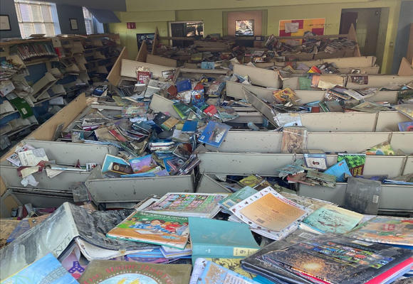 Floor of the Caldwell Public Library in New Jersey littered with wet books following heavy rains from Hurricane Ida.