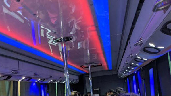 Cover for Driver shortages force students to go on field trip in bus with dance poles and neon lights