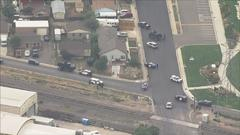 Cover for Large Number Of Law Enforcement Authorities Surround Home In Commerce City