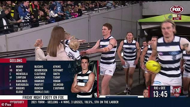 Picture for Mystery brunette linked to Gary Rohan is spotted with the AFL star AGAIN - planting a kiss on his cheek and handing him his kids as he took to the field for his 150th game